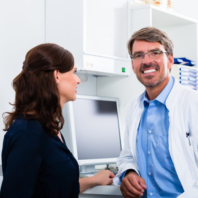 """General practitioner in doctors office seeing patient"" stock image"