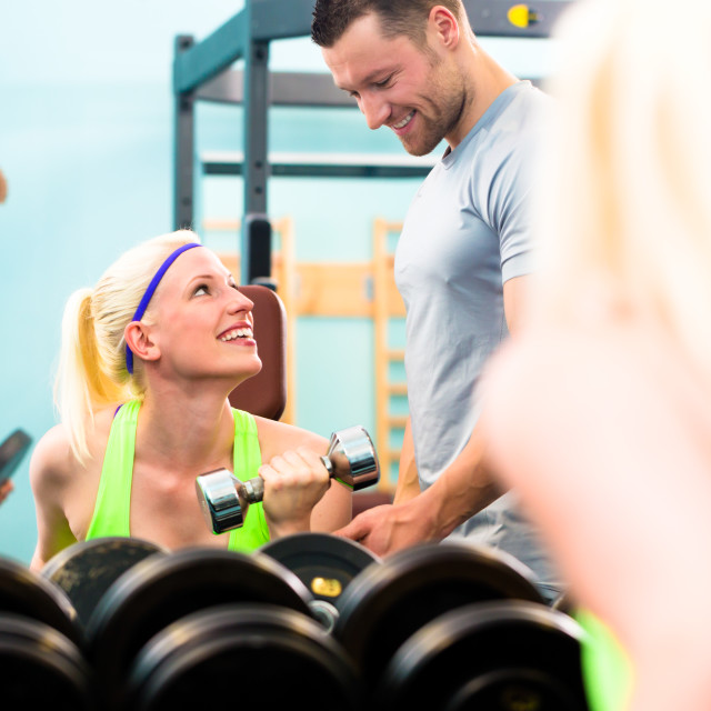 """""""Woman in gym training with dumb bells"""" stock image"""