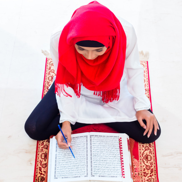 """Asian Muslim woman studying Koran or Quran"" stock image"