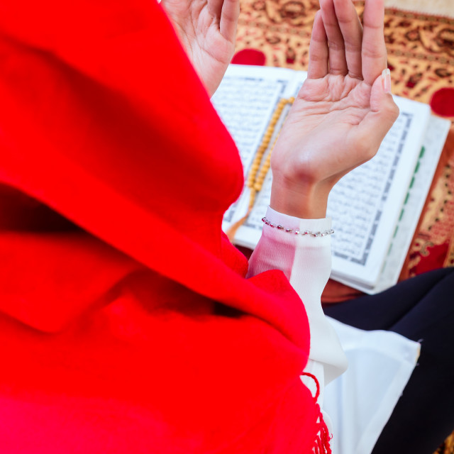 """Asian Muslim woman praying with Koran"" stock image"