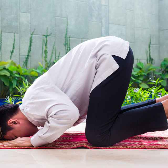"""Asian Muslim man praying on carpet"" stock image"