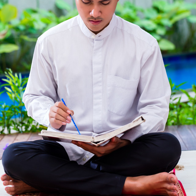 """Asian Muslim man studying Koran or Quran"" stock image"