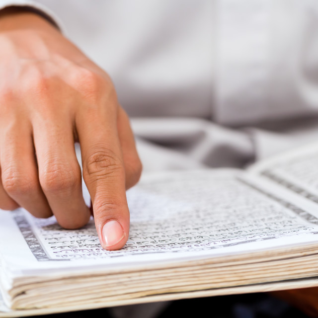 """Asian Muslim man studying Koran or Quran"" stock image"