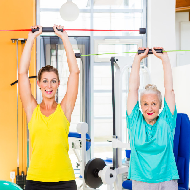"""""""Young and old woman in gym training strength with rod"""" stock image"""
