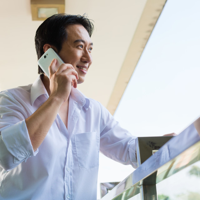"""Asian man telephoning on balcony with mobile phone"" stock image"