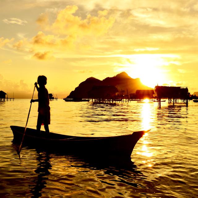 """Bajau Laut kid paddling a boat"" stock image"