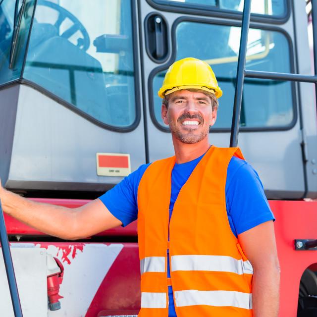 """Crane operator standing proud on company yard"" stock image"