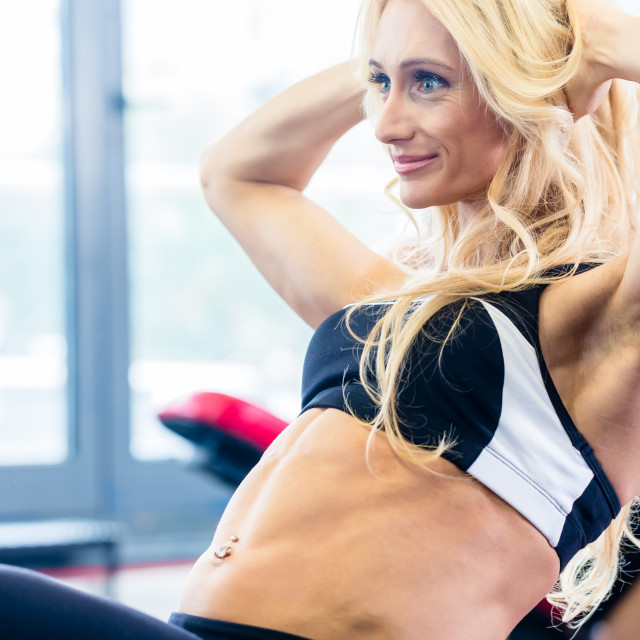 """""""Bodybuilding woman doing sit-up in fitness gym"""" stock image"""