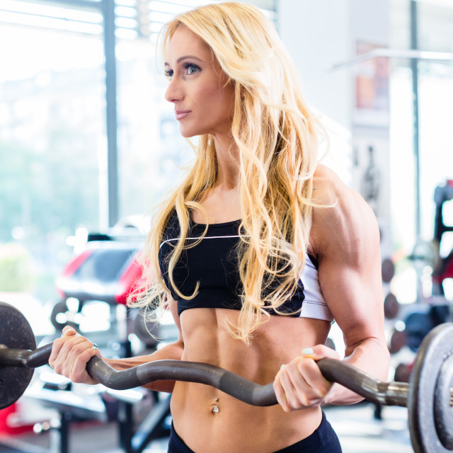 """""""Woman with barbell doing sport in fitness gym"""" stock image"""