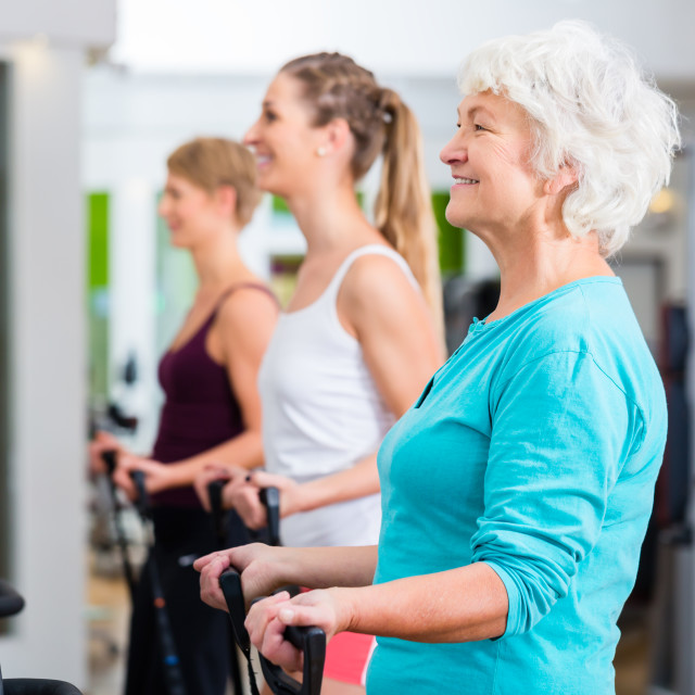 """Old and young people on vibrating plates in gym"" stock image"