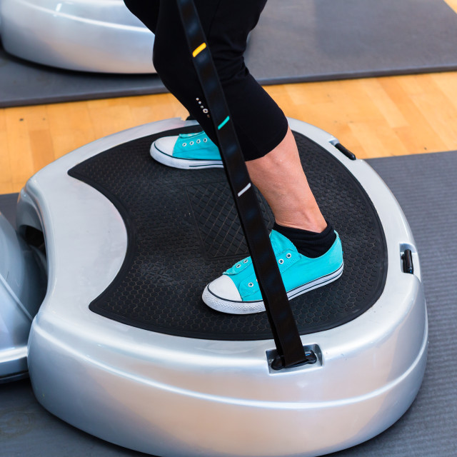 """Woman on vibrating plates in gym training"" stock image"