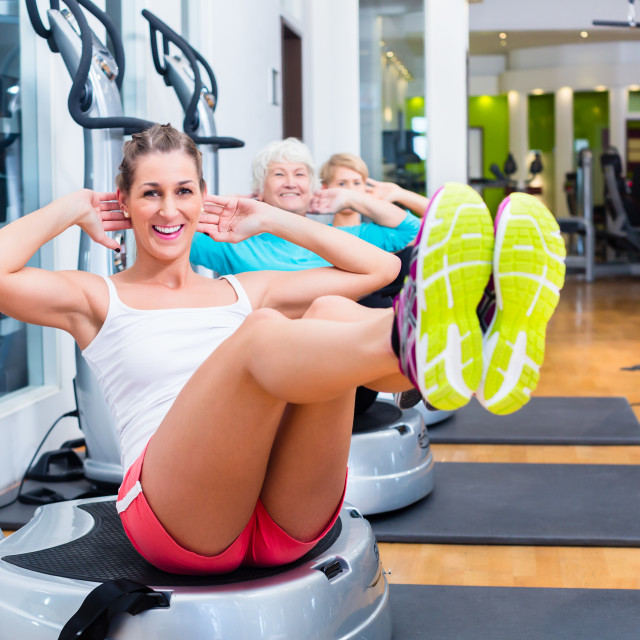 """Group on vibrating plates in gym training"" stock image"