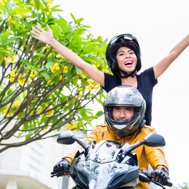 """Indonesian woman feeling free on motorcycle"" stock image"