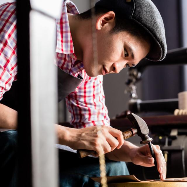 """Asian shoe or belt maker in his leather workshop"" stock image"