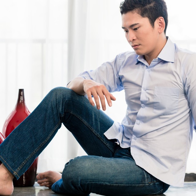 """Depressed Asian man sitting on apartment floor"" stock image"
