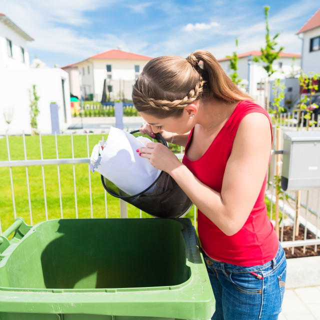 """Woman throwing waste paper away in container"" stock image"