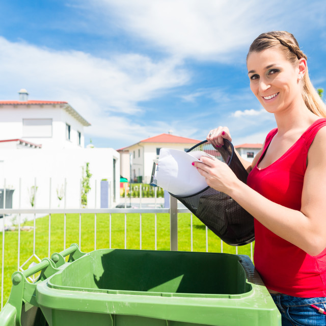 """Woman emtying trash or garbage into litter box"" stock image"