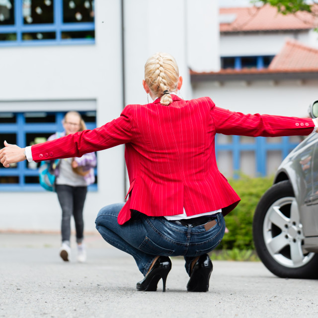 """""""Mother hugging child after bringing her to school"""" stock image"""