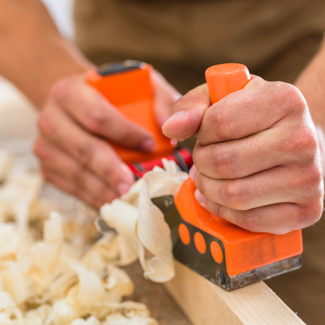 """""""Carpenter with wood planer working on piece"""" stock image"""