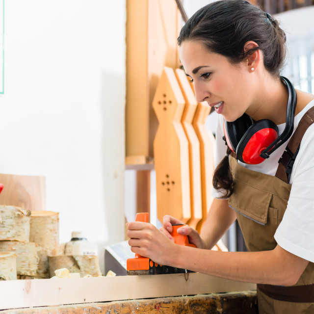 """""""Carpenter woman working with planer in her workshop"""" stock image"""