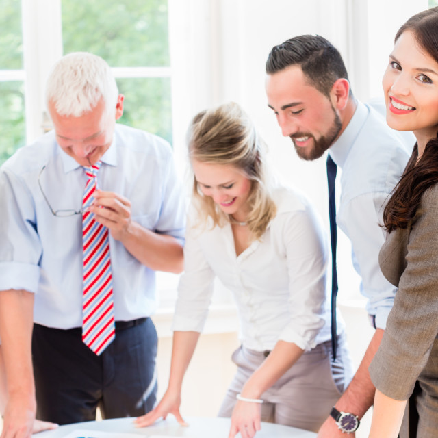"""Business team in strategy meeting discussing"" stock image"