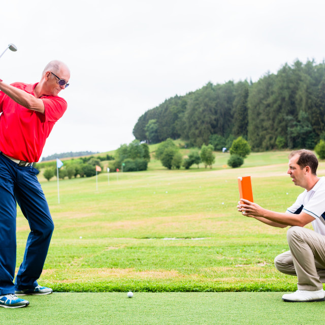 """Golf trainer recording video of senior golf player"" stock image"