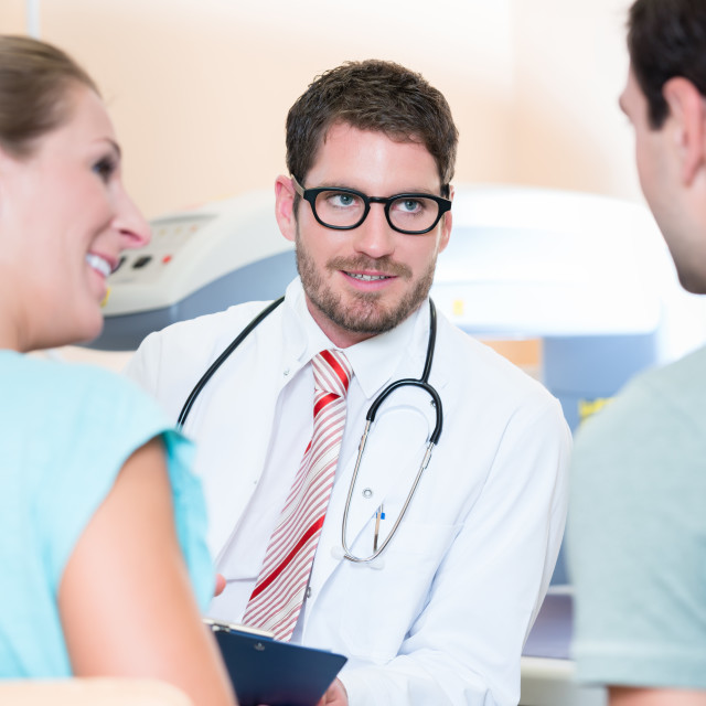 """Pregnant woman and her partner seeing physician"" stock image"