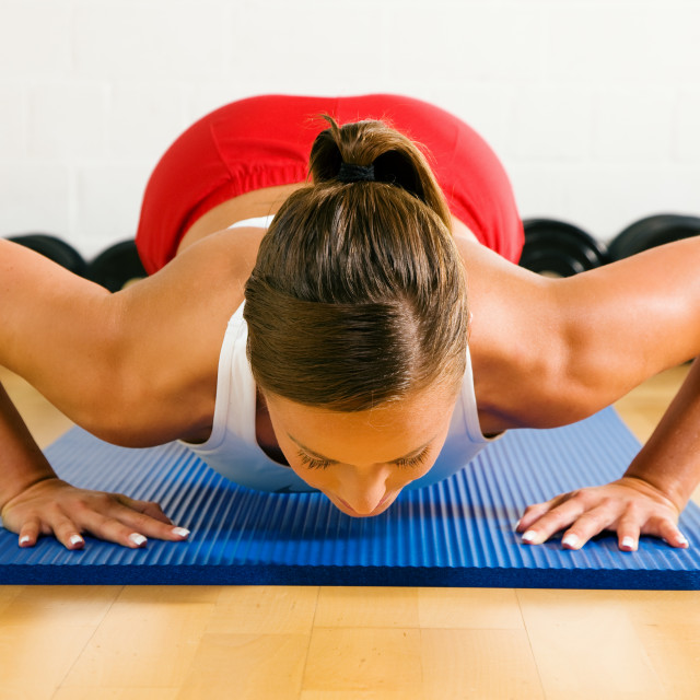 """woman doing pushups in gym"" stock image"
