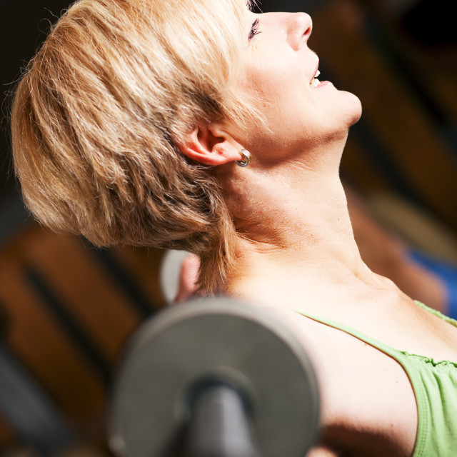 """Mature woman lifting barbell"" stock image"