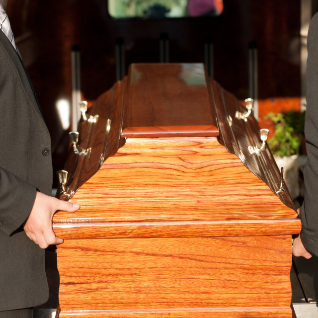 """Funeral with casket carried by coffin bearer"" stock image"