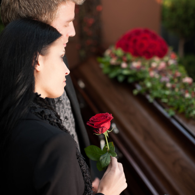 """Mourning Couple at Funeral with coffin"" stock image"