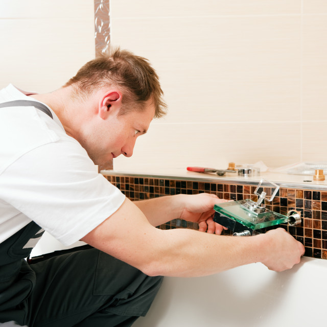 """Plumber installing a mixer tap in a bathroom"" stock image"