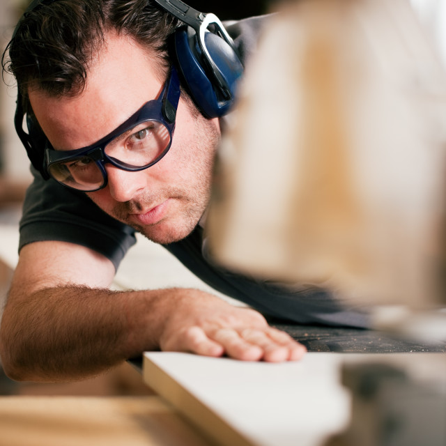"""Carpenter using electric saw"" stock image"