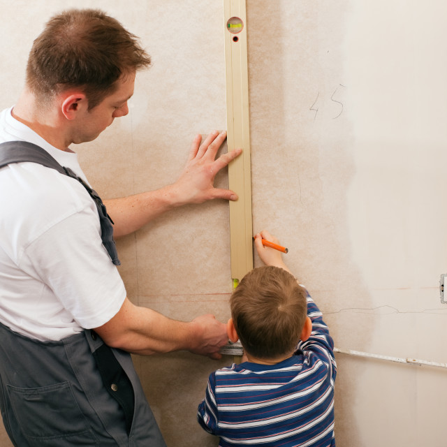 """Father and son measuring dry wall"" stock image"
