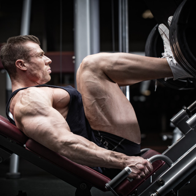 """Man in gym training at leg press"" stock image"