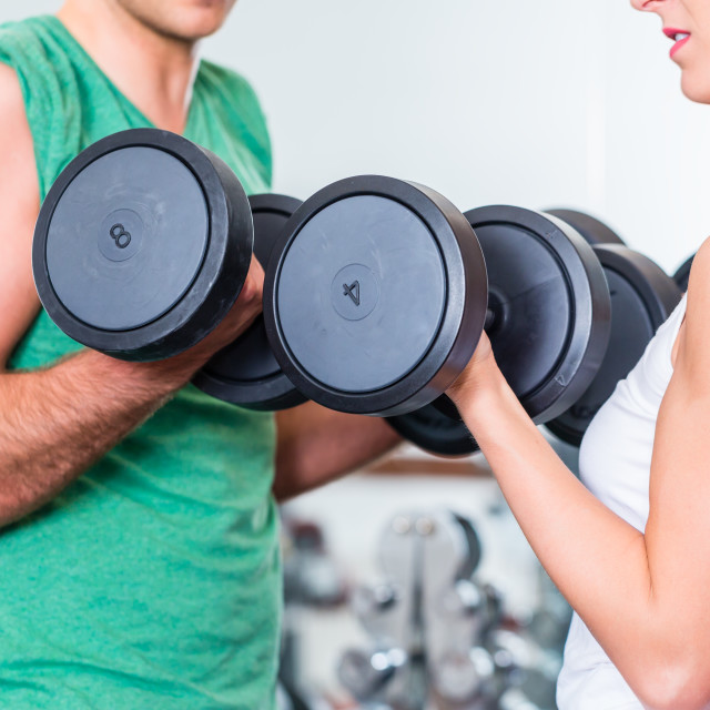 """young couple in gym lifting dumbbell"" stock image"