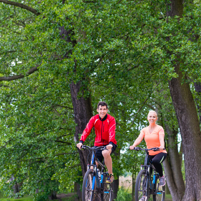 """Woman and man on mountain bike in the woods"" stock image"
