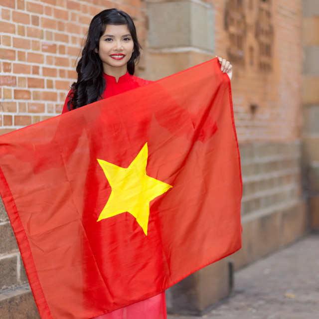 """Pretty young Vietnamese woman holding a flag"" stock image"