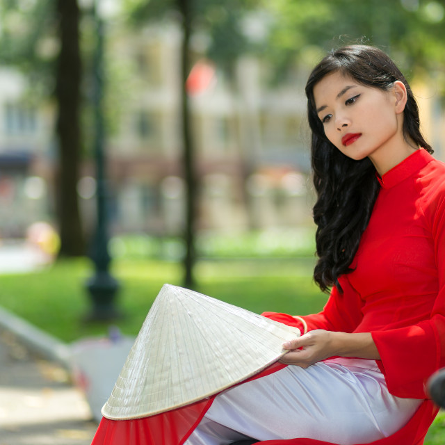 """Sad young Vietnamese woman sitting on a bench"" stock image"
