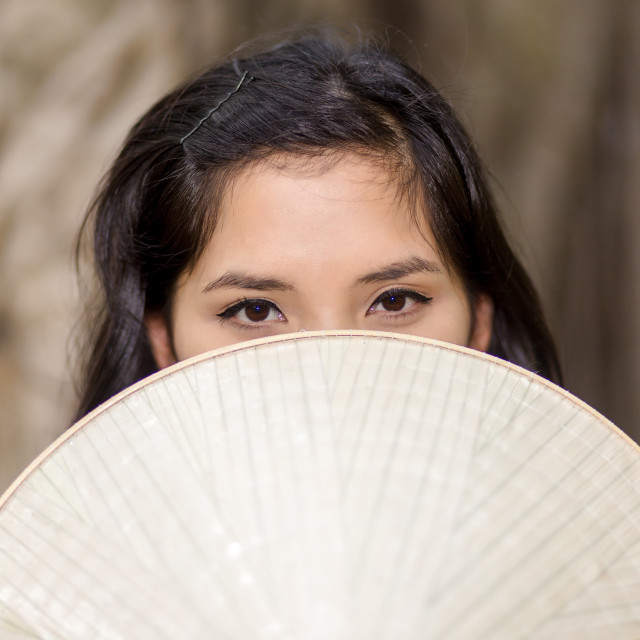 """Mysterious Woman Covering Half Face with Fan"" stock image"