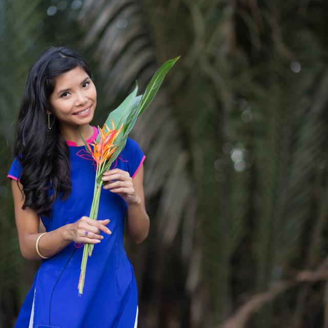 """Smiling Vietnamese Woman Holding Fresh Flowers"" stock image"