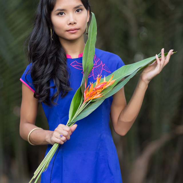 """""""Young Woman in Blue Ao Dai Holding Flowers"""" stock image"""