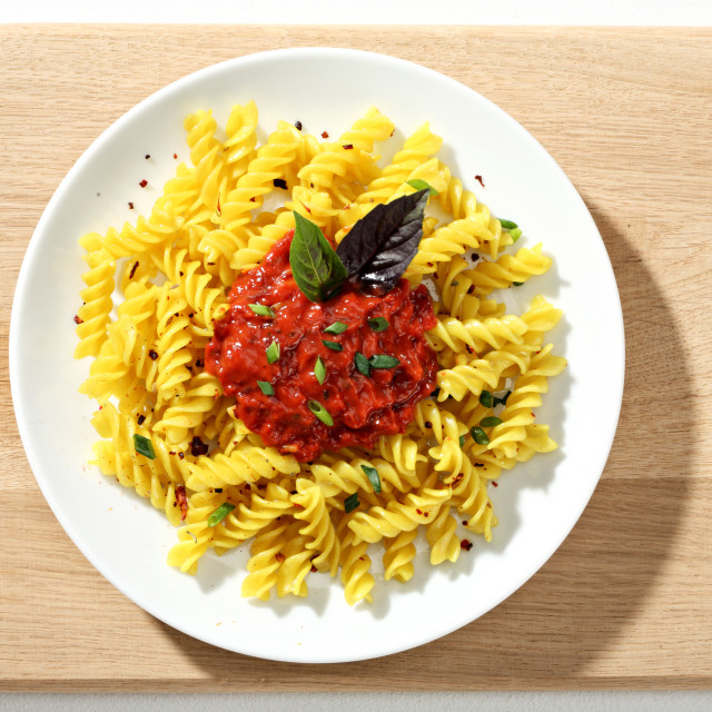 """Macaroni fusilli with tomatoes sauce in white ceramic plate on wooden cutting board. Close up, top view, high resolution product."" stock image"
