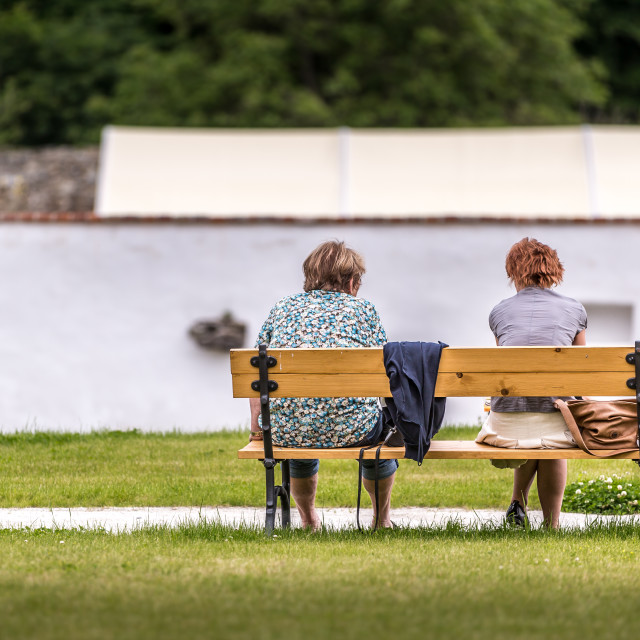 """Two ladies sitting on a bench in the sunshine"" stock image"