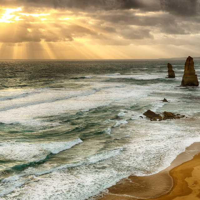 """HDR effect on Twelve Apostles sea rocks during sunset with dramatic rays. Twelve Apostles in one of attraction in Port Campbell National Park along the road of Great ocean road."" stock image"