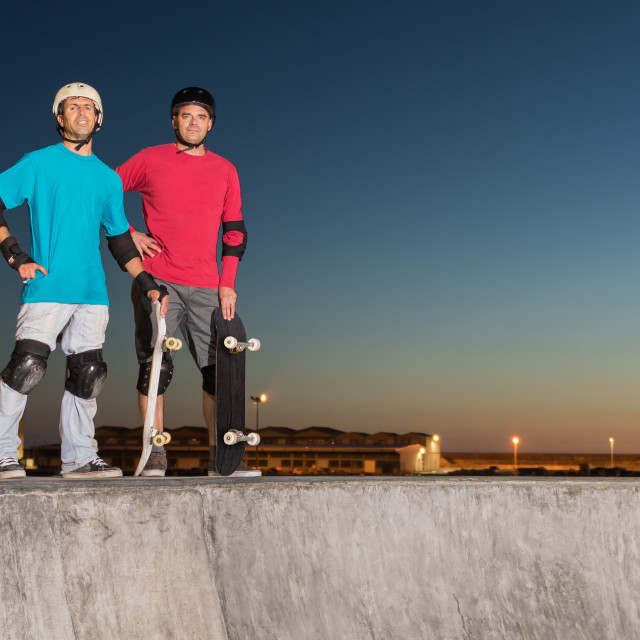 """""""Two skateboarders standing near a concrete pool"""" stock image"""