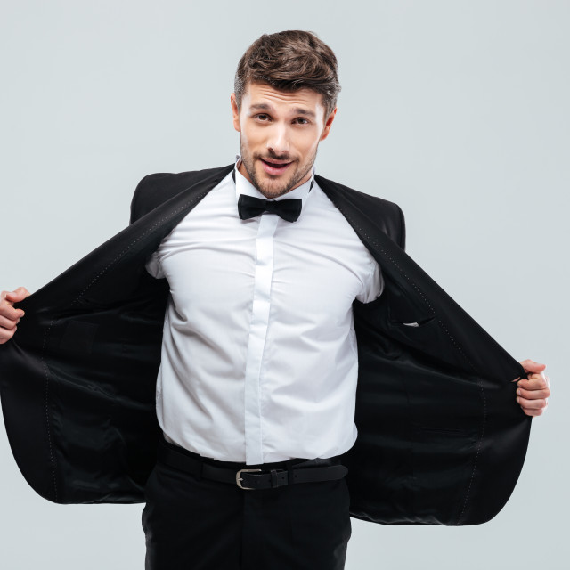 """""""Smiling young man in tuxedo taking off his jacket"""" stock image"""