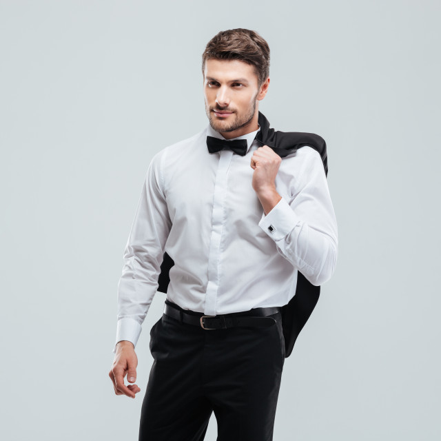 """""""Handsome young man in tuxedo with bowtie holding his jacket"""" stock image"""
