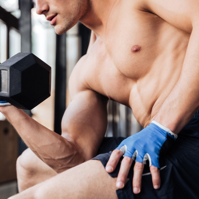 """Cropped image of a bodybuilder workout with dumbbell in gym"" stock image"