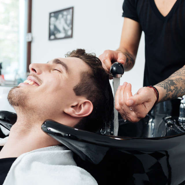 """Hairstylist washing client's hair in barber shop"" stock image"